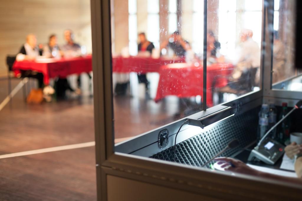 Interpretación simultánea en una cabina de interpretación durante una conferencia
