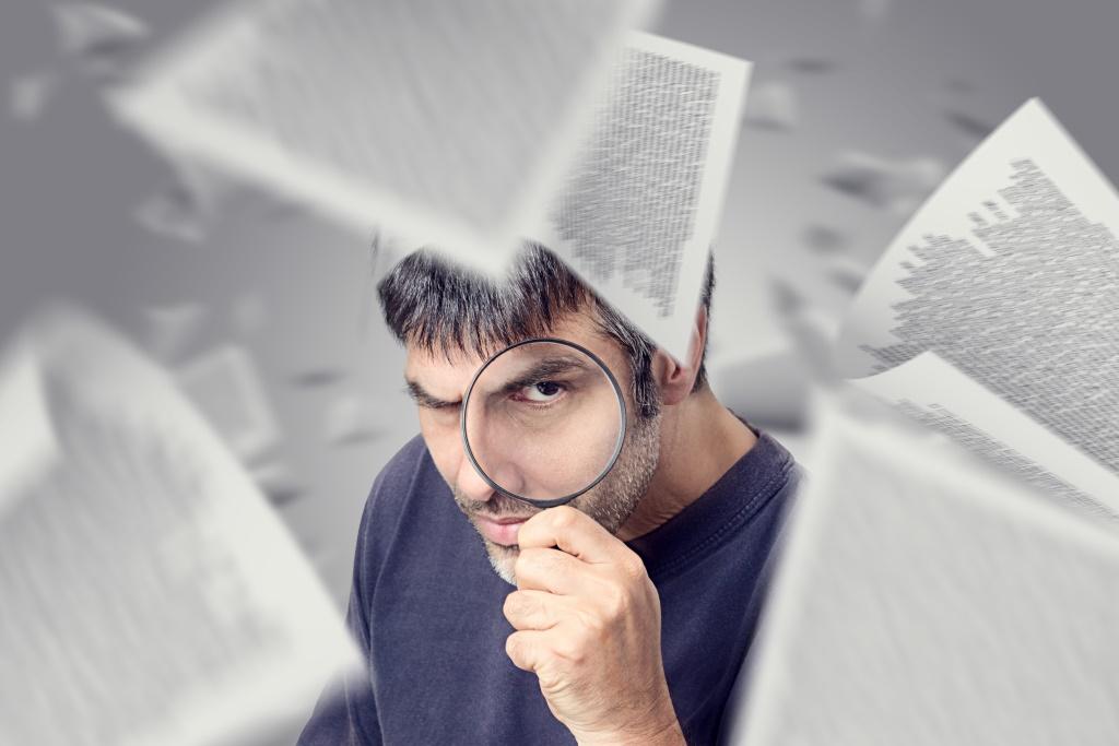 Hombre revisando textos con una lupa