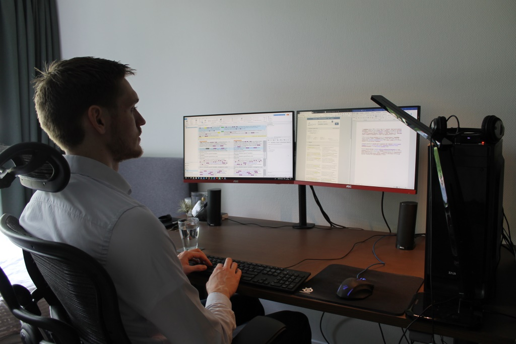 Wiebe translating at desk with computer and lamp